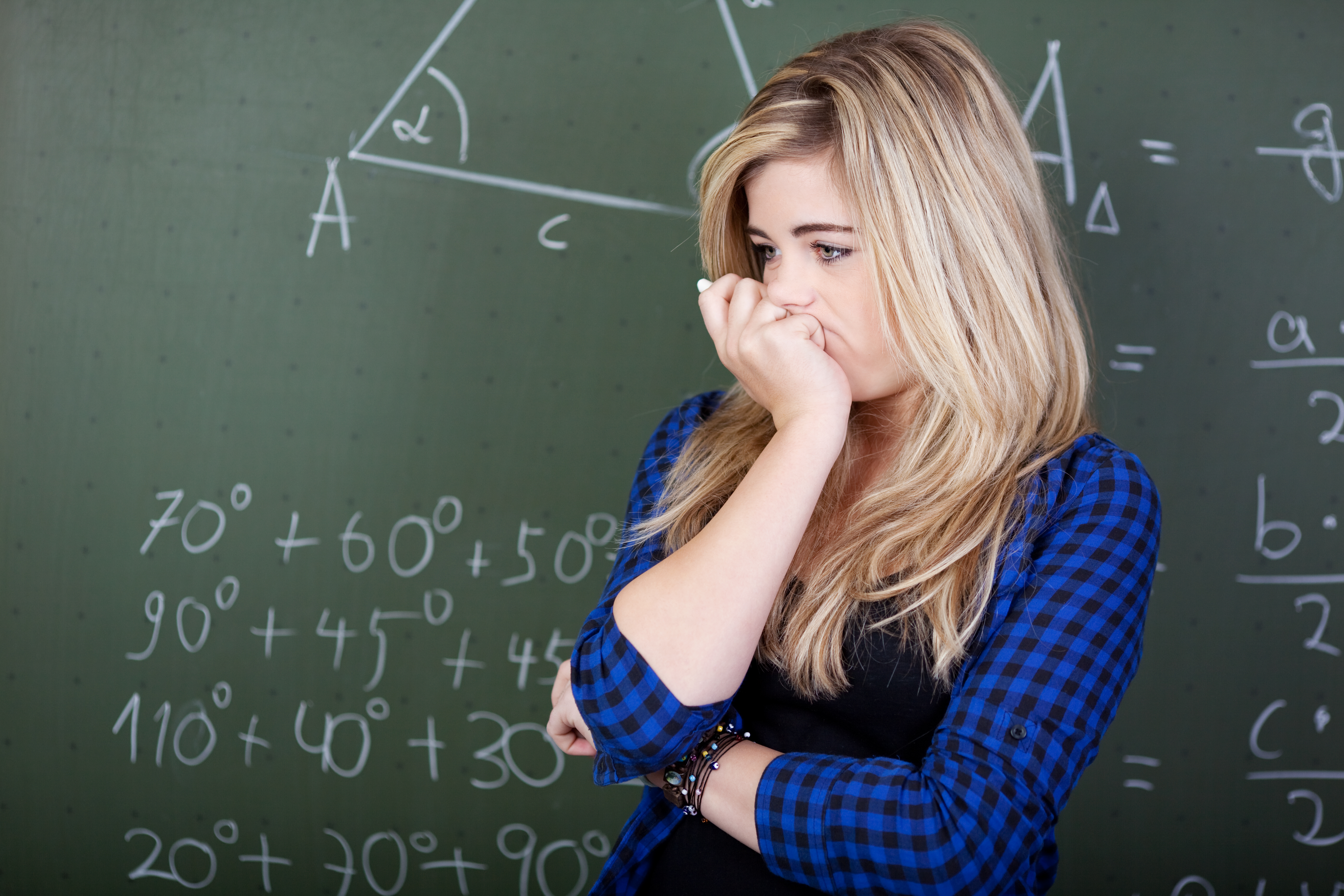 Female student deep thoughts standing at blackboard
